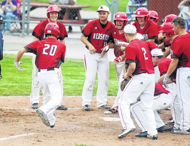 Wapakoneta's Don Goodes is greeted at home plate by teammates as he scores after hitting agrand slam against Maumee during Saturday's Division II district final game at Garrold Parratt Field in Hamler.