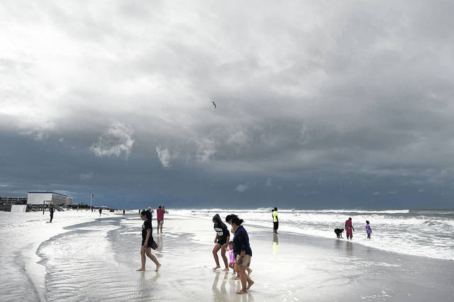 Beachgoers walk on Okaloosa Island in Fort Walton Beach, Fla., Monday, May 28, 2018, as Subtropical Storm Alberto approaches the Gulf Coast. The storm's gusty rain and brisk winds roiled the seas near the U.S. Gulf Coast on Monday, keeping white sandy beaches emptied of their usual Memorial Day crowds.
