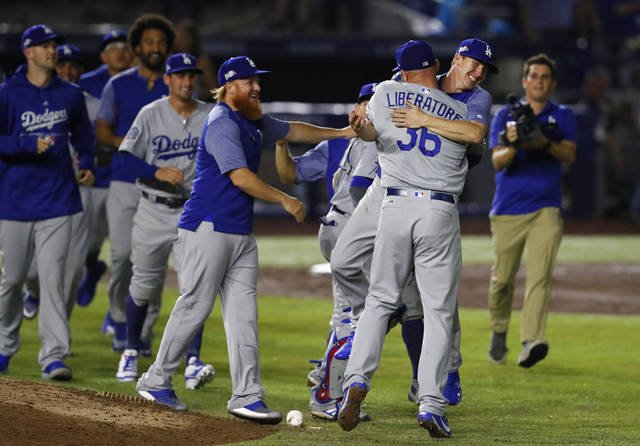 Los Angeles Dodgers relief pitcher Adam Liberatore is hugged by a teammate after the team's 4-0 win over the San Diego Padres in a baseball game in Monterrey, Mexico, Friday, May 4, 2018. Rookie Walker Buehler and a trio of Los Angeles relievers combined for the franchise's 23rd no-hitter in a 4-0 victory in the opener of a neutral-site series. (AP Photo/Eduardo Verdugo)