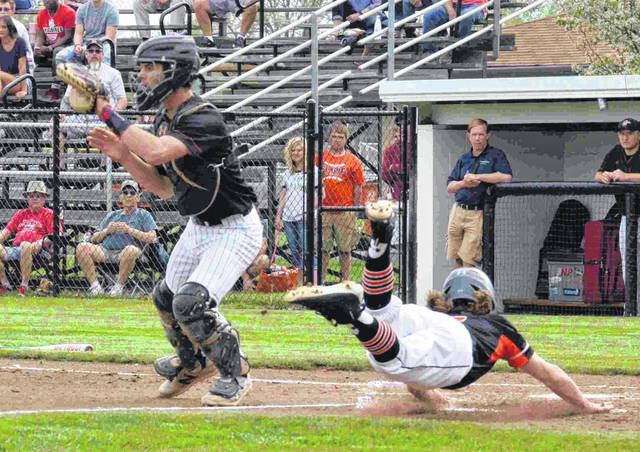 Elida Bulldog Matt Fish dives safely to home plate as Shawnee Indain catcher Jake Cowan awaits the throw in a game at Ed Sandy Field.