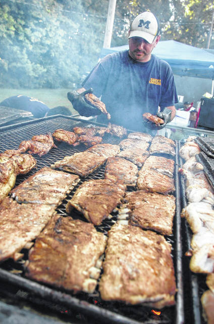 Matt Reynolds, of Lima, grills half racks of ribs and half chickens for Sweet Carolines BBQ during a past Star Spangled Spectacular at Faurot Park in Lima.