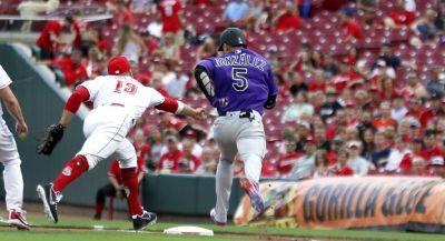 The Reds' Joey Votto is unable to tag out Colorado's Carlos Gonzalez during Tuesday night's game in Cincinnati.