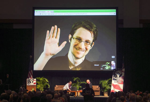FILE - In this Feb. 14, 2015, file photo, Edward Snowden appears on a live video feed broadcast from Moscow at an event sponsored by ACLU Hawaii in Honolulu. Snowden blew the lid off U.S. government surveillance methods five years ago. The 34-year-old is living in exile in Russia, but intelligence chiefs complain that revelations from the trove of classified documents he disclosed keep trickling out.(AP Photo/Marco Garcia, File)