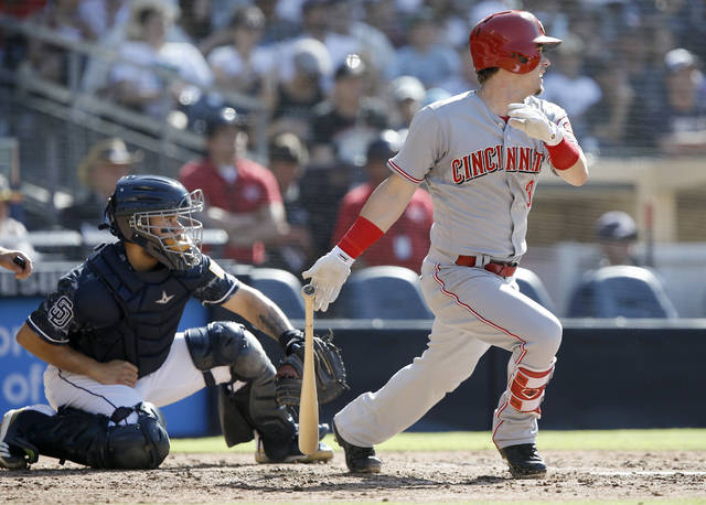 Cincinnati Reds' Scooter Gennett, right, hits an RBI single to score Jesse Winker, with San Diego Padres catcher Raffy Lopez watching, during the fifth inning of a baseball game in San Diego, Sunday.