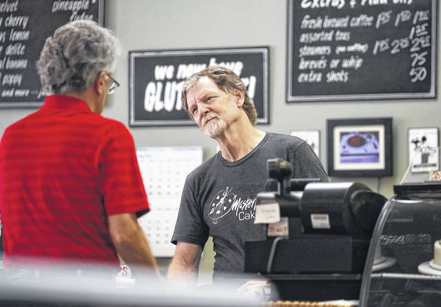 Baker Jack Phillips, owner of Masterpiece Cakeshop, right, manages his shop Monday in Lakewood, Colo. The Supreme Court ruled Monday in favor of Phillips, who wouldn't make a wedding cake for a same-sex couple, in a limited decision that leaves for another day the larger issue of whether a business can invoke religious objections to refuse service to gay and lesbian people.