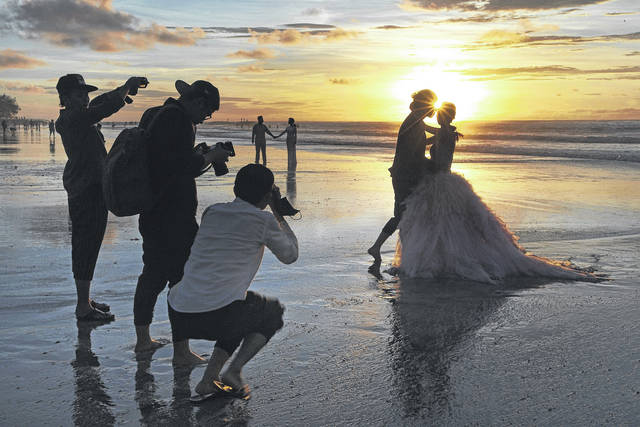 In this Jan. 18, 2017, file photo, photographers take photos of a tourist couple's wedding at the famous Kuta beach during sunset in Bali, Indonesia. According to a 2016 survey from wedding site The Knot, the average cost of an international destination wedding is $25,800. That figure may be within your event budget, but for guests, international airfare and multinight lodging could be out of reach.