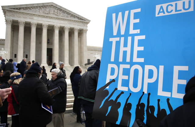 FILE - In this Jan. 10, 2018, file photo, people rally outside of the Supreme Court in opposition to Ohio's voter roll purges in Washington. The Supreme Court is allowing Ohio to clean up its voting rolls by targeting people who haven't cast ballots in a while. The justices are rejecting, by a 5-4 vote on June 11, 2018, arguments that the practice violates a federal law that was intended to increase the ranks of registered voters.(AP Photo/Jacquelyn Martin, File)