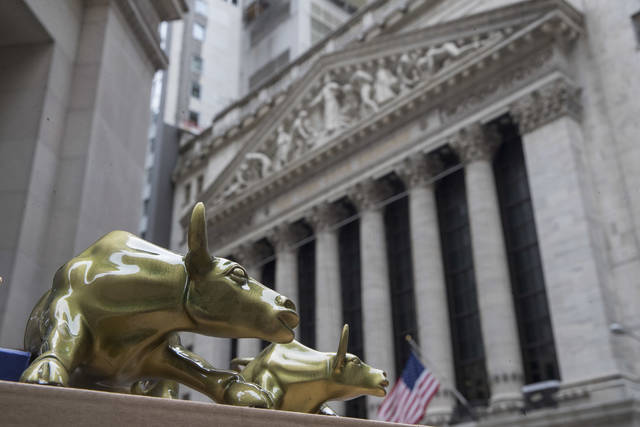 "FILE- In this April 24, 2018, file photo, replicas of Arturo Di Modica's ""Charging Bull"" are for sale on a street vendor's table outside the New York Stock Exchange. The U.S. stock market opens at 9:30 a.m. EDT on Wednesday, June 13. (AP Photo/Mary Altaffer, File)"