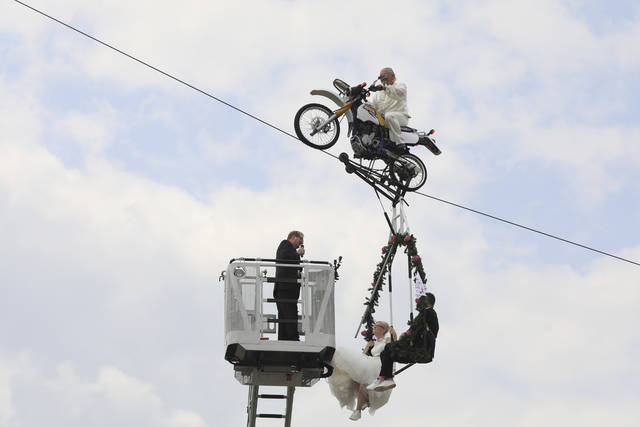 Pastor Stefan Gierung, left, stands in a cage atop of a fire service ladder in front of bride Nicole Backhaus, center, and groom Jens Knorr, right, both sitting in a swing dangling under a motorcycle with artist Falko Traber, top, during the wedding ceremony atop a tightrope in Stassfurt, Germany, Saturday, June 16, 2018. (Peter Gercke/dpa via AP)