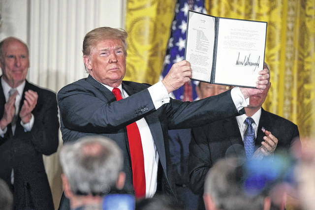 "President Donald Trump shows off a ""Space Policy Directive"" after signing it during a meeting of the National Space Council in the East Room of the White House, Monday in Washington."