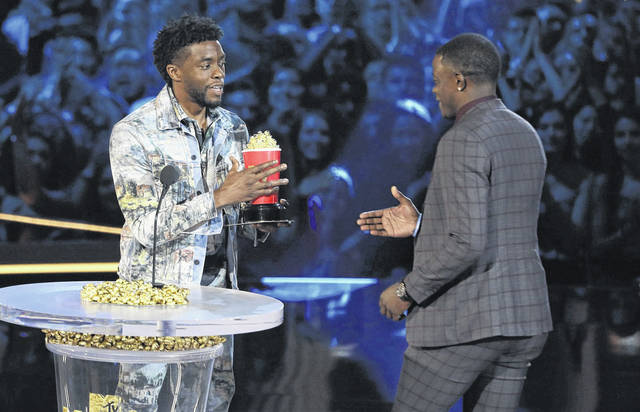 """In this Saturday, June 16, 2018, photo, Chadwick Boseman, left, gives his best hero award for his role in """"Black Panther"""" to James Shaw Jr., who is credited with saving lives during a shooting at a Waffle House in Antioch, Tenn., at the MTV Movie and TV Awards at the Barker Hangar in Santa Monica, Calif. (Photo by Matt Sayles/Invision/AP)"""