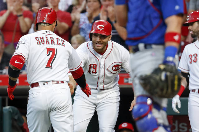 Cincinnati Reds' Eugenio Suarez (7) celebrates with Joey Votto (19) after hitting a two-run home run off Chicago Cubs starting pitcher Jose Quintana during the fifth inning of a baseball game Friday.
