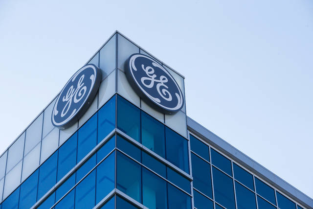 FILE- In this Jan. 16, 2018, file photo, the General Electric logo is displayed at the top of their Global Operations Center in the Banks development of downtown Cincinnati. A year after taking over an ailing American conglomerate, CEO John Flannery is calving off larger chunks of General Electric, spinning off its health care business and selling its stake in the oil services company, Baker Hughes. (AP Photo/John Minchillo, File)