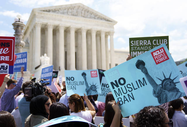 Protesters hold up signs and call out against the Supreme Court ruling upholding President Donald Trump's travel ban outside the the Supreme Court in Washington, Tuesday.