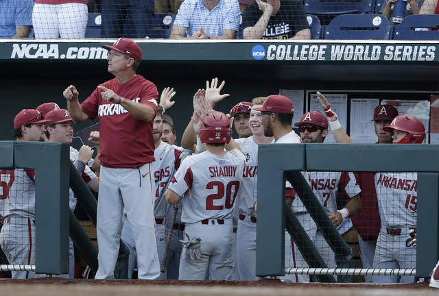 Arkansas coach Dave Van Horn, foreground left, gestures as Carson Shaddy (20) is congratulated by teammates after scoring a run against Oregon State during the fifth inning of Game 1 of the NCAA College World Series baseball finals in Omaha, Neb., Tuesday.