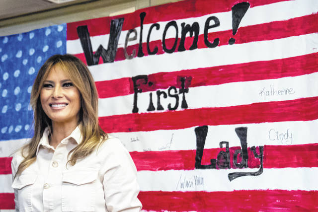 First lady Melania Trump smiles after signing American flag artwork while visiting the Upbring New Hope Children Center run by the Lutheran Social Services of the South in McAllen, Texas, Thursday, June 21, 2018.