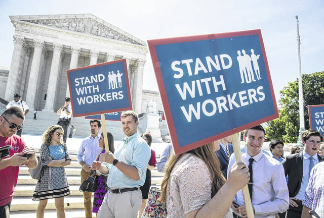 In this Monday photo, people gather at the Supreme Court awaiting a decision in an Illinois union dues case, Janus vs. AFSCME, in Washington. The Supreme Court says government workers can't be forced to contribute to labor unions that represent them in collective bargaining, dealing a serious financial blow to organized labor.