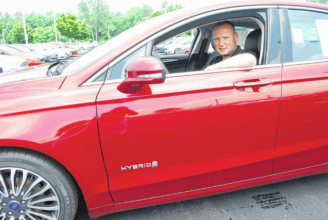J Swygart | The Lima News  Blake Cole, new car manager at Reineke Ford, sits behind the wheel of a Ford Fusion hybrid vehicle. Cole said the Lima dealership typically tries to keep a half-dozen or more hybrid vehicles on the lot at all times.