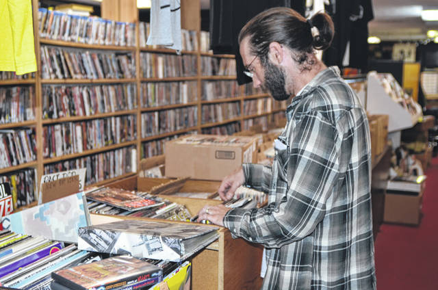 George Smed, of Bellefontaine, and member of the Gam Gam Buckmaster band, browses through records at Groamy's CD's and Tapes on 1206 W. Robb Ave.