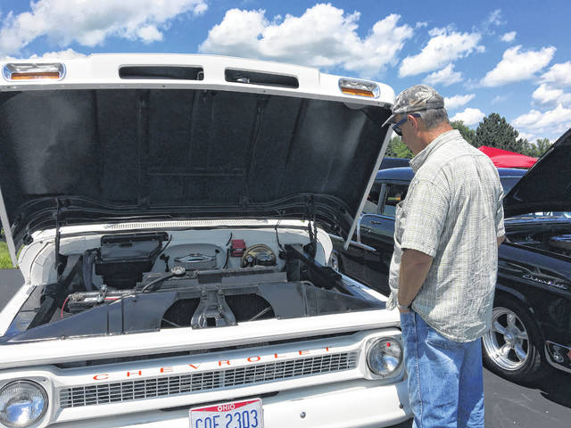 Steve Hall, of Lima, looks at the engine of a 1966 Chevy truck on display during the 10th annual Charity Car Show held Sunday at the Lima Chevrolet Cadillac dealership.