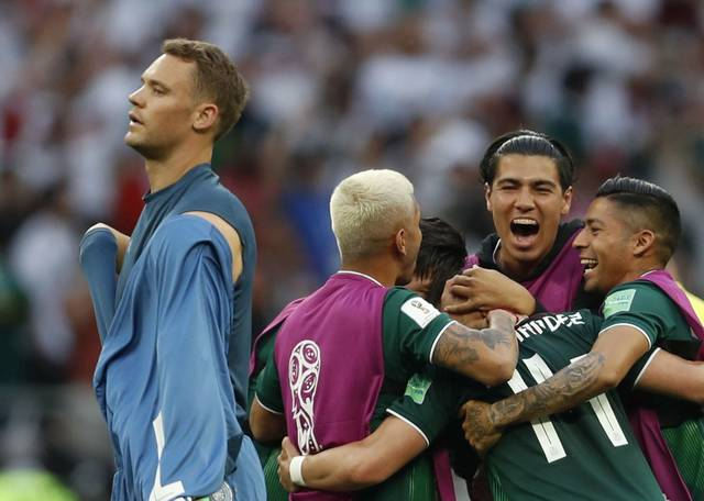 Mexican players celebrate while German goalkeeper Manuel Neuer walks off the field after Mexico defeated defending World Cup champion Germany 1-0 on Saturday in Moscow.