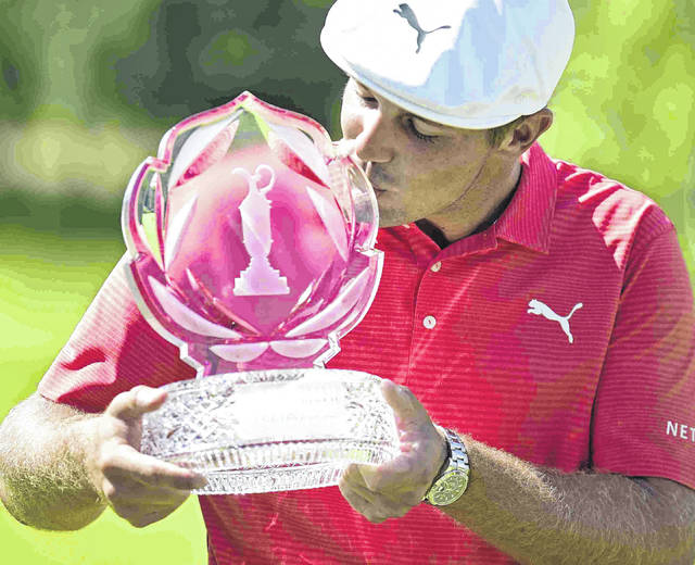 Bryson DeChambeau kisses the trophy after winning the Memorial Tournament after the final round of the Memorial golf tournament Sunday, June 3, 2018, in Dublin, Ohio. (AP Photo/David Dermer)