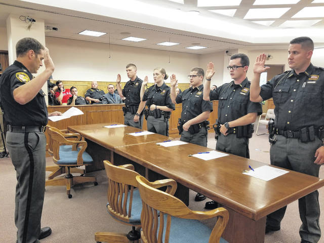 Allen County Sheriff Matt Treglia swore in five new deputies during a ceremony Wednesday evening in common pleas court. Pictured from left reciting the oath are Justin Hollar, Brianna Leary, Justin Jolliff, Logan Curfman and Dane Querry. Each new hire had a family member of their choice pin their first badge.