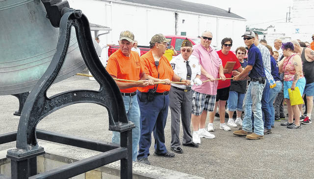 People line up to ring the bell at the archway of the Putnam County Fairgrounds in Ottawa to celebrate Monday's opening of the Putnam County Fair.