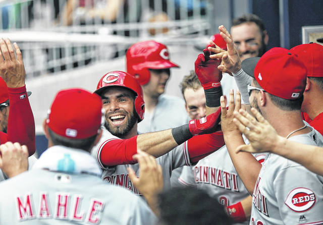 Cincinnati Reds' Jose Peraza (9) celebrates with teammates in the dugout after hitting a solo-home run in the third inning of a game against the Atlanta Braves on Wednesday.