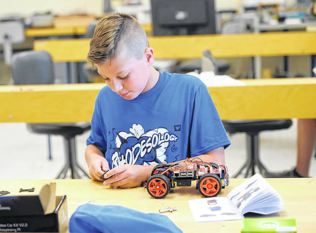 Gannon Casebolt, 12, creates a project at Rhodesology Summer Camps on Tuesday. The camp is offered annually by Rhodes State College which allows attendees to experience skilled concepts in engineering, sports and fitness, visual and written arts, aerodynamics, propulsion and resistance while building and launching a rocket.