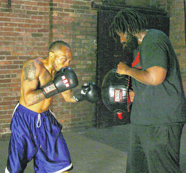 "Eddie Hines, left, works out with Marquis Valentine as the two prepare for big fights Saturday. Valentine is part of the main event and fighting for the unofficial title of ""best heavyweight in Ohio."""