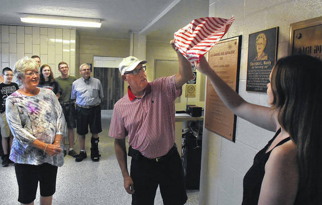 """Bryan Marshell, center, and daughter, Meredith, remove a cover from a bronze plaque of the """"Swimming Lady"""" Saundra Neely, left, during a surprise event at Ada Pool in the Ada War Memorial Park."""