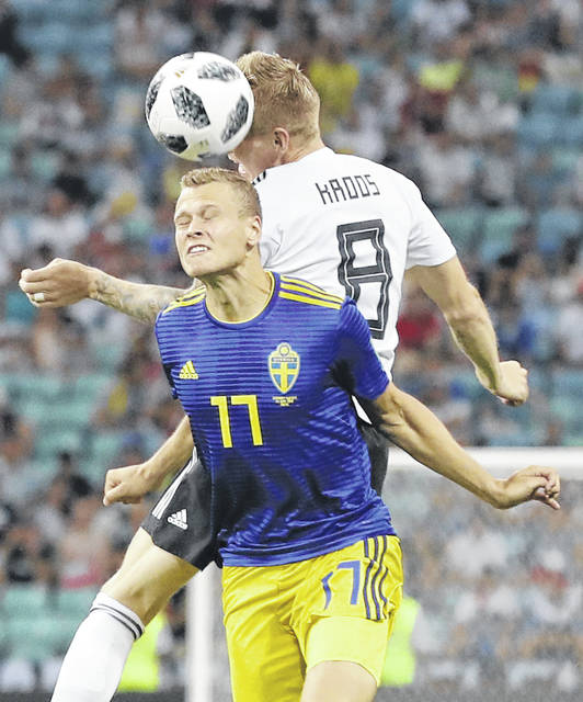 Sweden's John Guidetti, left, and Germany's Toni Kroos jump for the ball during the group F match between Germany and Sweden at the 2018 soccer World Cup in the Fisht Stadium in Sochi, Russia Saturday.