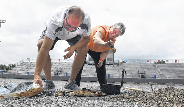 Former Lima Senior Athletic Director Jim Offenbaker, left, and athletic secreatary, Pam Sinica, remove the water damaged contents of a time capsule buried on the 50-yard line in the middle of the stadium on Wednesday.