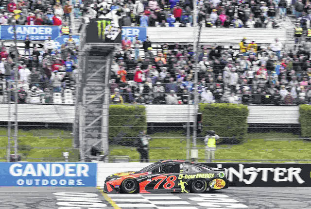 Martin Truex Jr. crosses the finish line to win a NASCAR Cup Series auto race Sunday, June 3, 2018, in Long Pond, Pa. (AP Photo/Derik Hamilton)