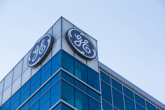 FILE- In this Jan. 16, 2018, file photo, the General Electric logo is displayed at the top of their Global Operations Center in the Banks development of downtown Cincinnati. On Tuesday, June 19, 2018, the S&P Dow Jones Indices said General Electric will be dropped from the Dow Jones industrial average the following week, ending the industrial conglomerate's more than 100-year run in the 30-company blue chip index. (AP Photo/John Minchillo, File)