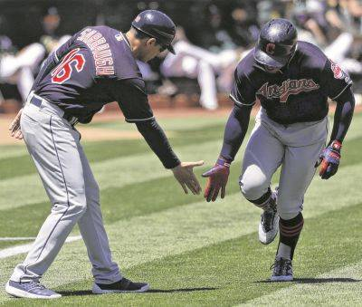 Cleveland coach Mike Sarbaugh congratulates the Indians' Francisco Lindor as Lindor heads for home after hitting a solo home run during Saturday's game in Oakland, Calif.