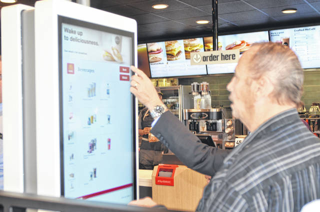 A customer is trying out the new ordering kiosks in the lobby of the newly rennovated McDonad's location on 2619 Elida Road Wednesday.