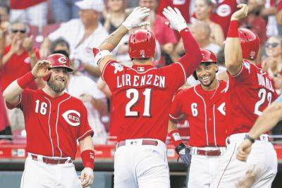 The Reds' Michael Lorenzen (21) is congratulated by teammates Adam Duvall (23), Billy Hamilton (6) and Tucker Barnhart (16) after knocking all three in with a home run during Saturday's game against Milwaukee in Cincinnati.