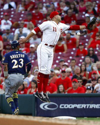 Milwaukee's Keon Broxton (23) reaches on an infield single against Reds first baseman Joey Votto (19) during the third inning of Thursday night's game in Cincinnati.
