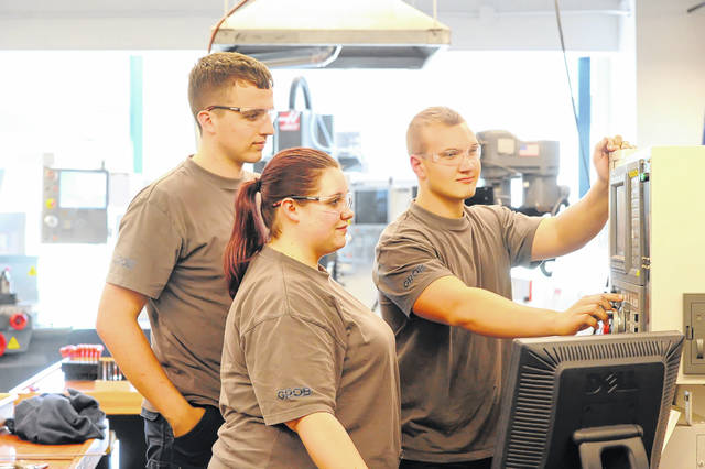 Connor Koch, Taylor Darnell and Jared Rieman work together during a class at Rhodes State College last week. The college's West Central Ohio Manufacturing Consortium offers a computer numerical control certification.