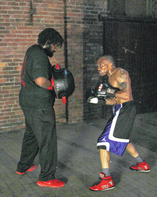 Marquis Valentine, left, assists Eddie Hines with his training as both boxers prepare for major bouts this Saturday.