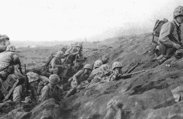 A photo of Iwo Jima, Feb. 19, 1945. Members of the 2nd Battalion, 23rd Marines take shelter on a terrace above the beach during D-Day as they form their battle plan after landing.