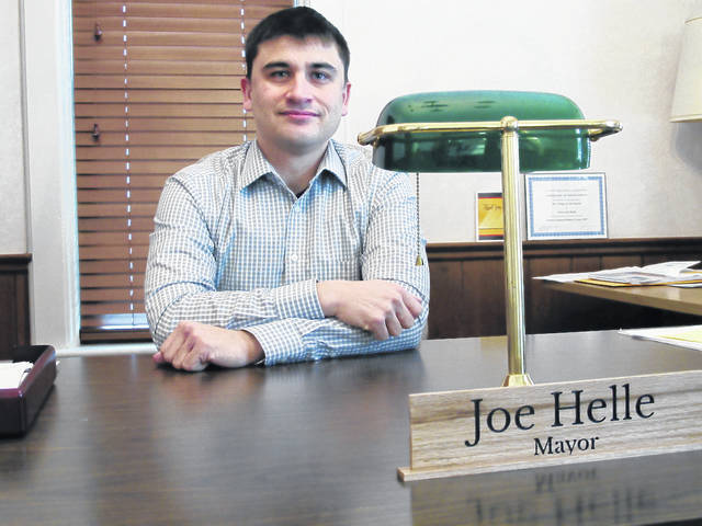 In this Dec. 27, 2017 photo, army veteran Joseph Helle poses in his mayor's office in Oak Harbor, Ohio. Helle was removed from the voting rolls in Ohio while serving in Iraq and Afghanistan.
