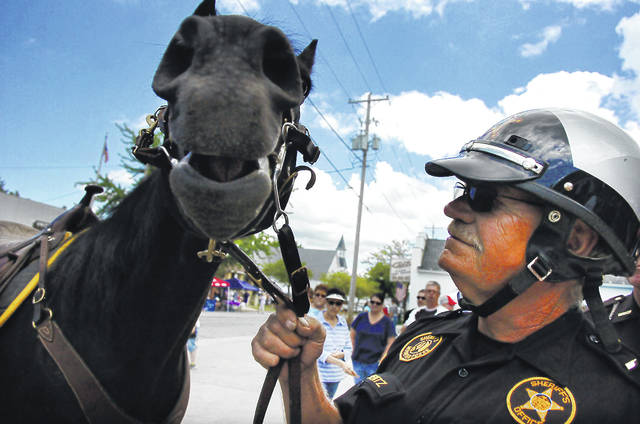 Jim Clementz, Allen County Sheriff's mounted posse unit, stands with his horse Walker before the blessing of the badges at a past Cridersville Fireman's Jamboree.