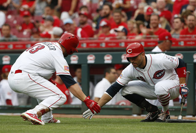 Cincinnati Reds' Scott Schebler, left, gets a low five from Joey Votto following a solo home run off Chicago White Sox starting pitcher James Shields during the first inning of a baseball game Monday.