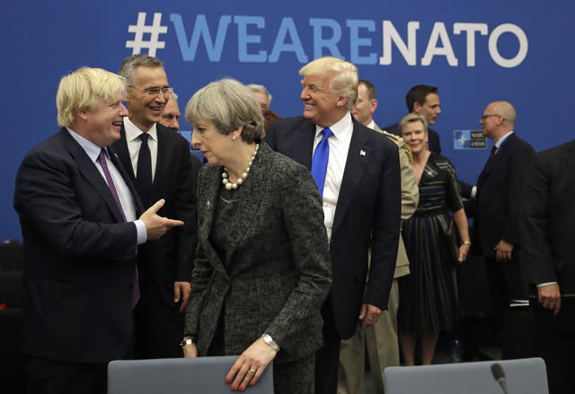 FILE - In this May 25, 2017, file photo, U.S. President Donald Trump jokes with British Foreign Minister Boris Johnson as British Prime Minister Theresa May walks past during a working dinner meeting at the NATO headquarters during a NATO summit of heads of state and government in Brussels. Threatening to upend generations of global order, Trump's week-long European trip will test the strained bonds with some of the United States' closest allies before putting him face-to-face with the leader of the country whose electoral interference helped put him in office.