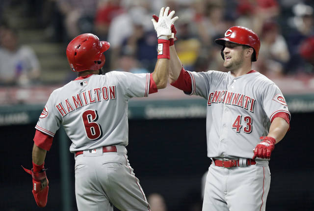 Cincinnati Reds' Scott Schebler, right, is congratulated by Billy Hamilton after Schebler hit a two-run home run off Cleveland Indians relief pitcher Josh Tomlin in the ninth inning of a baseball game Monday in Cleveland. Hamilton scored on the play.