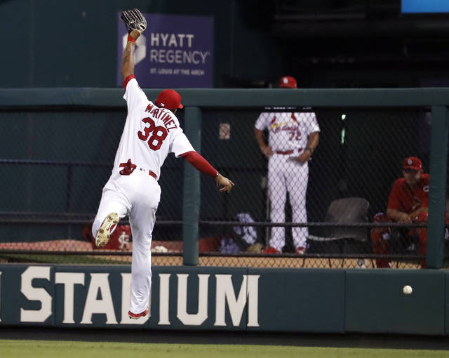 A double by Cincinnati Reds' Eugenio Suarez goes over the head of St. Louis Cardinals right fielder Jose Martinez during the fifth inning of a baseball game Friday, July 13, 2018, in St. Louis. (AP Photo/Jeff Roberson)