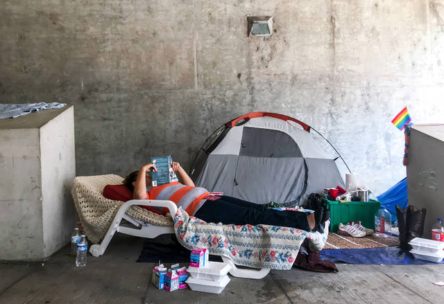 Latasha Butte, 22, reads from her lawn chair below an underpass in downtown Cincinnati on Monday, July 16, 2018. Dozens of homeless people were given 72 hours to vacate a downtown Cincinnati encampment consisting of tents, furniture and blankets under an order issued by city officials Monday. (AP Photo/Angie Wang)